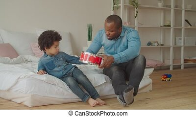 Positive mixed race boy playing toy drum at home