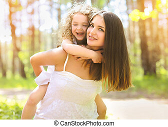 Positive mother and child having fun outdoors