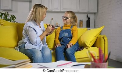 Positive mother applying make-up for her daughter - Pretty...