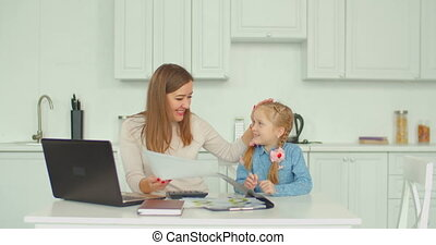 Positive mother calculating bills with daughter - Positive...