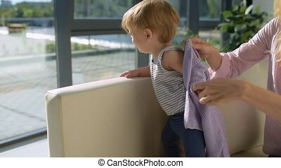 Positive mother dressing the child in the room