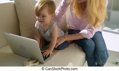 Positive mother with the child at the laptop