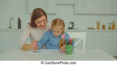 Positive mum and daughter drawing picture together