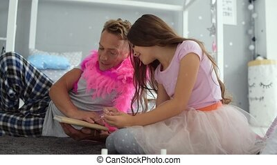 Positive nice girl painting nails of her father