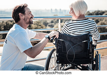Positive nice man helping a disabled woman
