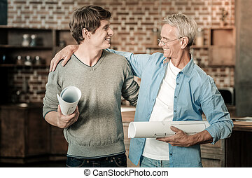 Positive nice man looking at his student