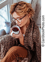 Positive nice woman enjoying her delicious coffee