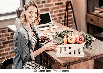 Positive nice woman sitting in front of the box with vegetables