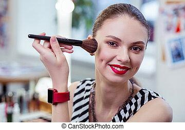 Positive nice woman using her makeup brush