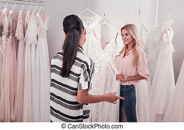 Positive nice young women discussing wedding dresses -...