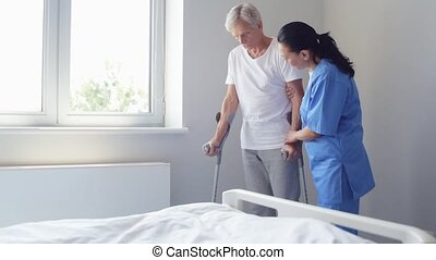 Positive nurse helping an aged man to walk on crutches - I...