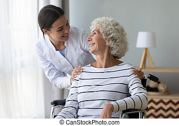 Positive nurse take care of elderly disabled woman