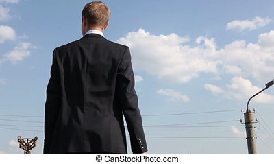 Young business guy viewed from all sides observing the city with a positive look