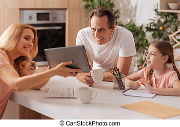 Positive parents enjoying painting with kid at home