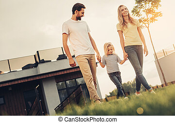 Positive parents going with optimistic child outdoor