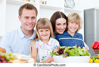 Positive parents preparing dinner with their children in the kitchen