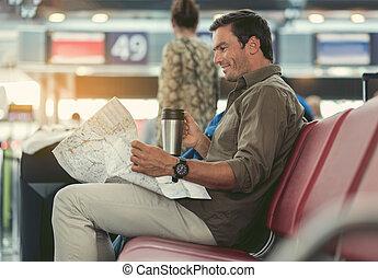 Positive pleasant adult traveler is exploring his route