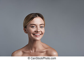 Positive portrait of smiling happy woman standing against...