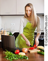 housewife with notebook in home kitchen