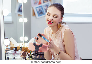 Positive pretty woman holding her professional mascara