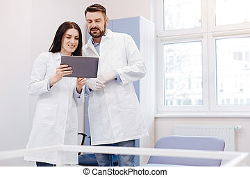 Positive professional doctors working with a tablet