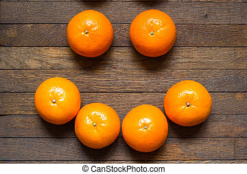 Positive raw foods concept. Mandarins laid out in the smile shape.