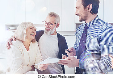 Positive real estate agent talking with elderly couple