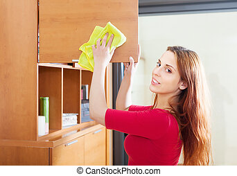girl wiping the dust from wooden furniture