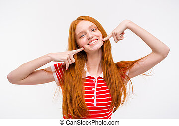 Positive redhead young woman touching her cheeks with fingers