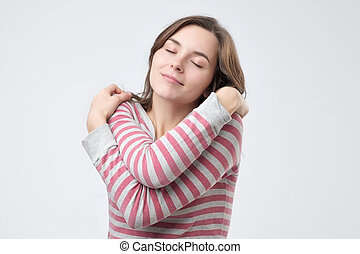 Positive relaxed woman closing eyes with pleasure, keeping arms around herself