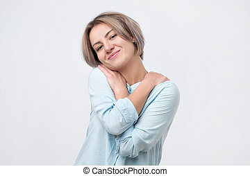 Positive relaxed young woman smiling with pleasure, keeping arms around herself