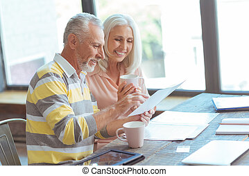 Positive retired couple counting their budget