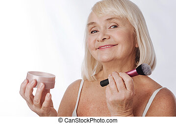 Positive retired woman using a makeup brush
