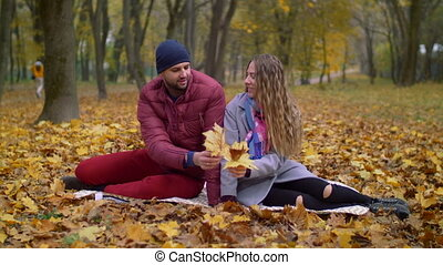 Positive romantic couple relaxing in autumn park -...