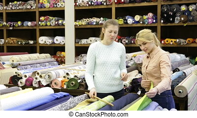 salesgirl working in fabrics store, offering advice to young...