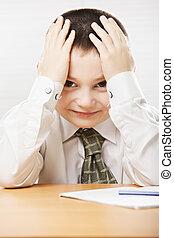 Positive schoolboy at the desk