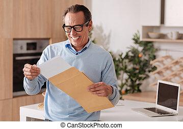 Positive senior businessman working at home