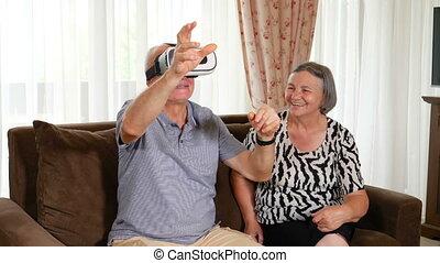Positive senior couple trying up virtual reality glasses -...