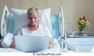 Positive senior in patient lying in a hospital bed