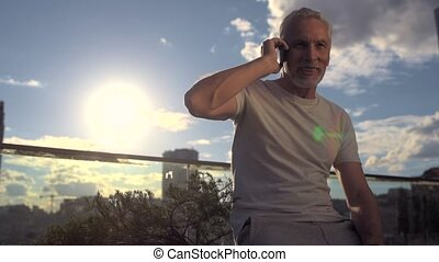 Positive senior man enjoying a conversation on phone