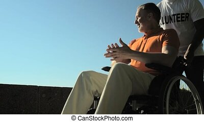 Positive senior man enjoying a walk in the wheelchair