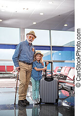 Positive senior man is posing with cute child - Full length...