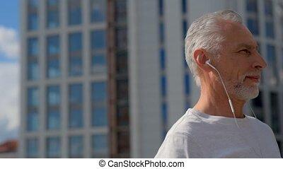 Positive senior man listening to music