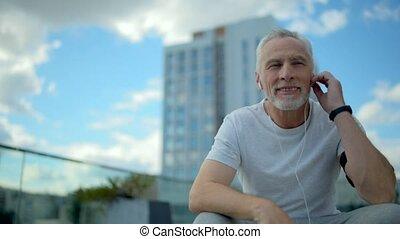 Positive senior man resting after sport activities