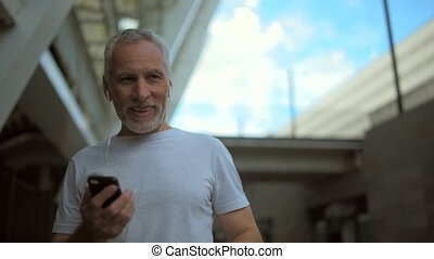 Positive senior man talking via smart phone - Glad to see...
