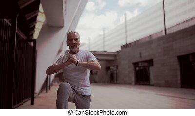 Positive senior man warming up before running