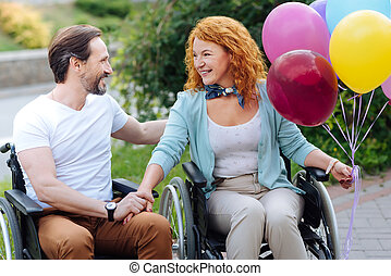 Positive senior wheelchaired couple resting in the park