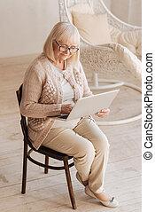 Positive senior woman holding a laptop