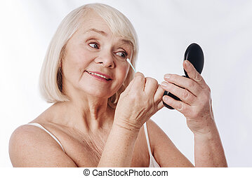 Positive senior woman looking into the mirror
