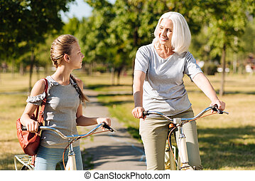 Positive senior woman riding bicycle with her granddaughter